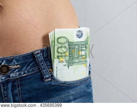 A Stack Of One-hundred-euro Bills Protrudes From The Front Pocket Of The Women's Jeans. A Woman's Ba