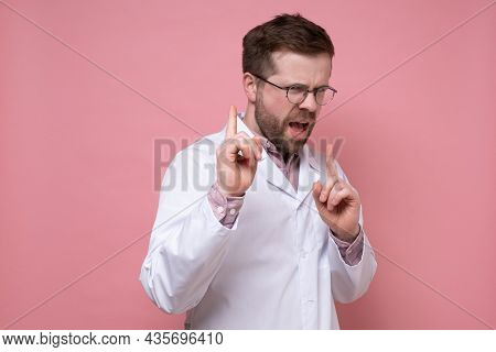 Disgruntled Doctor In A White Coat Scolds Someone, Pointing Strictly With Fingers. Pink Background.