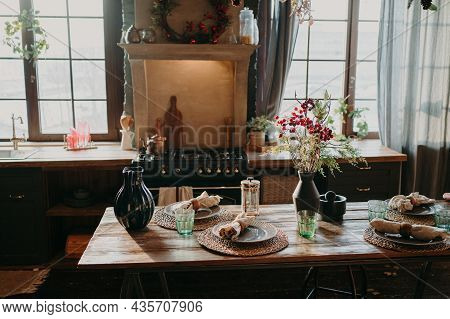 Interior Of Kitchen. Served Dining Table With Plates Glasses Floral Decor. Cutlery And Glassware. Pr