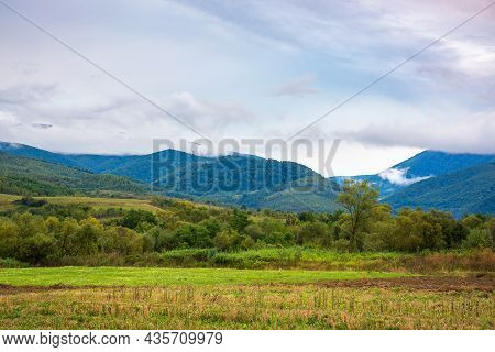 Rural Field In Mountains At Dawn. Cloudy Early Autumn Weather