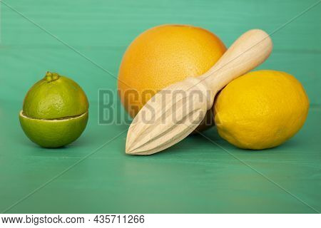 Lime Lemon Orange With A Wooden Hand Press On A Textured Turquoise Background. There Is A Place For
