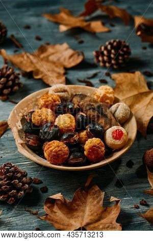 plate with some roasted chestnuts, a roasted sweet potato, and some panellets, typical confection of Catalonia, Spain, eaten traditionally in All Saints Day, in a party called Castanada, on a table