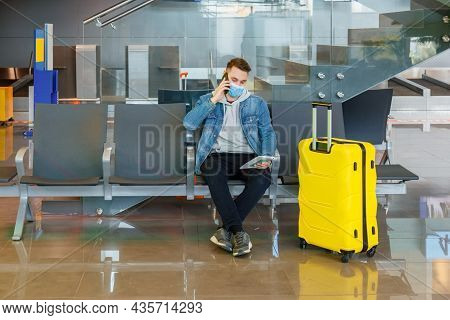 Attractive Young Man Talking On Phone In Airport Lounge With Big Yellow Suitcase Before Traveling By