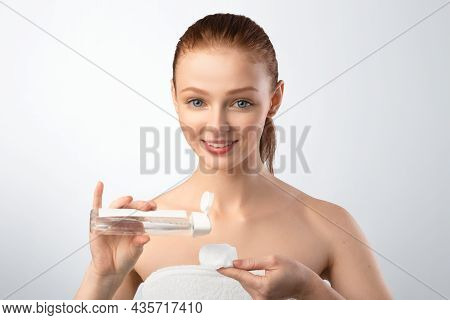 Red-haired Teen Girl Applying Lotion On Cotton Pad, Gray Background