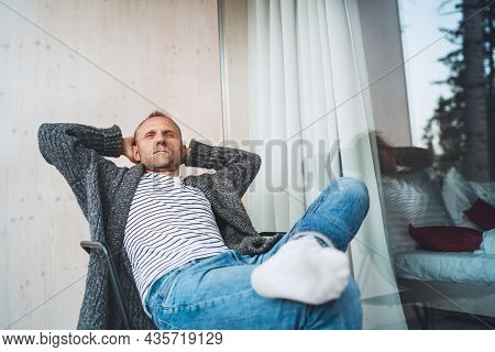 Portrait Of A Middle-aged Man Dressed Open Cardigan, Jeans, And Warm Socks Sitting On Forest House B