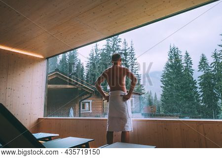 Relaxing Man Wrapped White Towel After Finnish Sauna In Tepidarium With Wide Window Enjoying The Gre