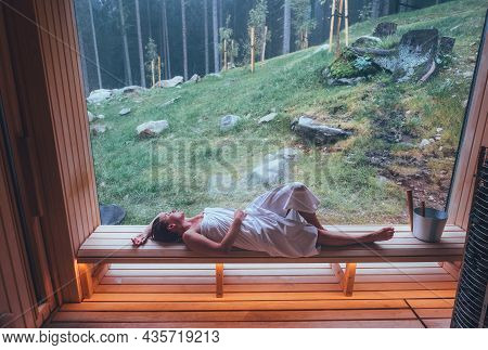 Relaxing Woman Wrapped White Towel In Hot Finnish Sauna With A Huge Wide Window Enjoying The Green F