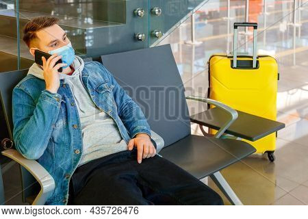Portrait Of Attractive Young Man Talking On Smart Phone In Airport Lounge With Suitcase Before Trave