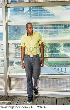 Wearing A Light Yellow Shirt, Gray Pants And Black Shoes,  A Young Black Guy Is Standing By A Big Gl