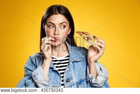 Girl Licking Her Fingers After Trying Delicious Pizza Slice, Looking At Food With Tempting Expressio