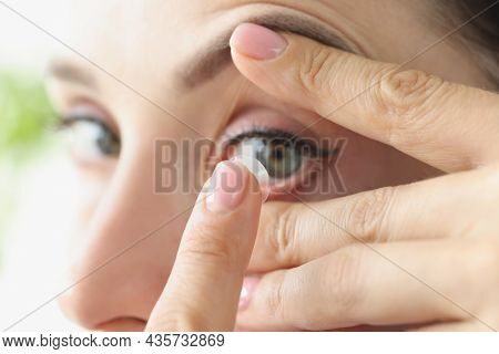 Woman Puts On Soft Contact Lens Over Eyes Closeup