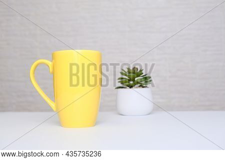 Big Yellow Ceramic Mug, Cup Of American Coffee On A White Table With A Potted Plant Against Light Br