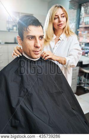 Barber Adjusting Paper Collar On Male Neck