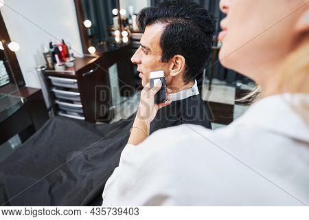 Beauty Salon Specialist Shaving Man Cheek With Shaver