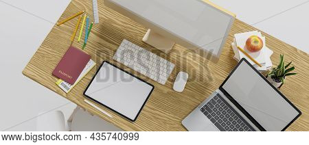 Top View Of Wooden Computer Desk With Computer, Tablet And Laptop Blank Screen Mockup