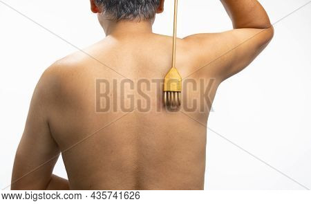 Senior Man Scratching His Back With A Back Scratcher.