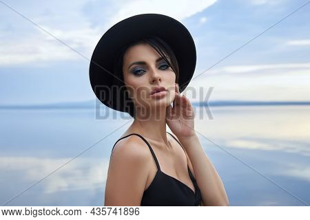 Perfect Brunette Beauty Woman In A Black Hat And A Black Dress Poses Near A Lake Against A Blue Sky.
