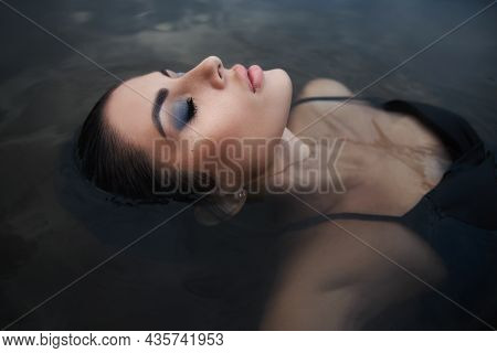 Beauty Brunette Woman In A Black Dress Poses In A Sea Lake Against A Blue Sky Background. Long Hair