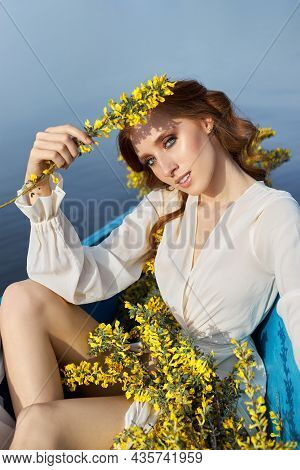 Redhead Woman In White Negligee Dress Sit In Blue Boat On Pond Lake. Red-haired Girl With Yellow Flo