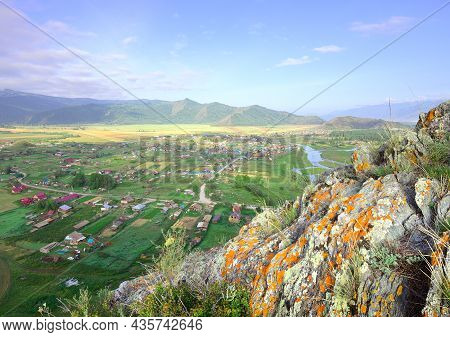The Edge Of A Cliff Above A Mountain Valley Under A Blue Cloudy Sky. Siberia, Russia