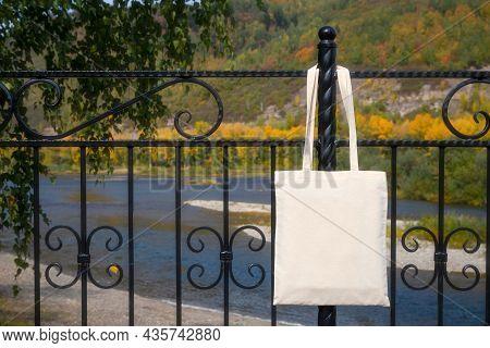 Canvas Tote Bag On The Bridge Railing Mockup. Rustic Linen Shopper Bag Mock Up For Branding Presenta