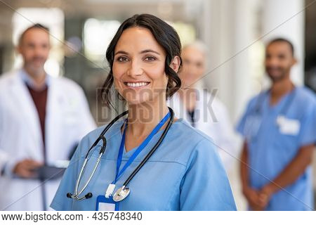 Portrait of happy young nurse in uniform with healthcare team in background. Successful team of doctor and nurses smiling. Beautiful and satisfied healthcare worker in private clinic looking at camera