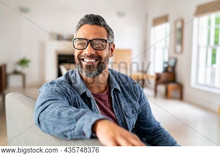 Happy mature middle eastern man wearing eyeglasses sitting on couch. Portrait of indian man relaxing at home and looking away with big smile. Mid adult guy with specs thinking about his future.