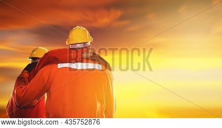 Back View Engineers, Machinists And Factory Workers Working Together Look At The Sunset Sky, Showing
