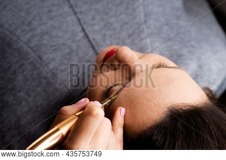 Young woman making tatouage for eyebrows in a dressing makeup room. Eyebrows make up process. Make-up artist in beauty studio doing makeup for beautiful girl. Making mua.