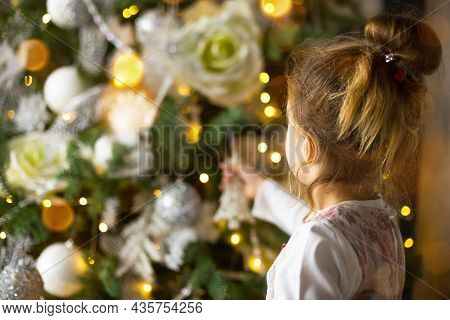 A Little Girl Reaches For A Christmas Tree Toy With Her Hand. Christmas Decor, Waiting For A Holiday