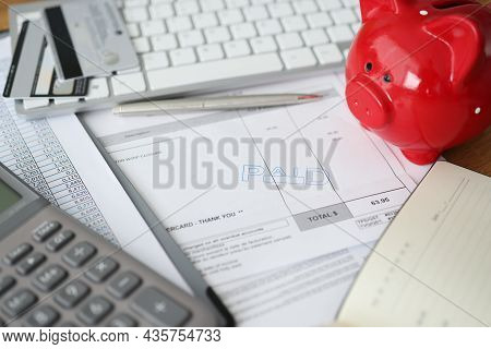 Invoice With Paid Stamp With Bank Cards And Piggy Bank On Table