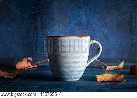 Autumn Still Life With A Cup Of Tea, Autumn Leaves, And Rain Behind The Window