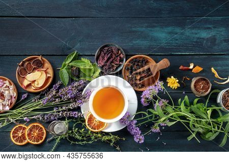 A Cup Of Tea With Dry Fruit, Flowers, And Herbs, Shot From Above On A Dark Rustic Wooden Background