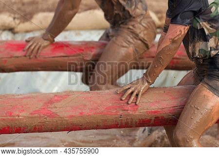 Mud Race Runners. Participants On The Tree Trunk, Catches Balance Above The Pit Full Of Water