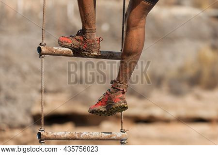Mud Race Runner. The Racer Overcomes The Obstacle By Climbing The Ladder
