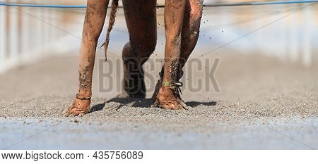 Mud Race Runners. Crawling, Passing Under A Wire Obstacles During Extreme Obstacle Race