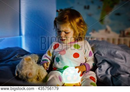 Cute Little Toddler Girl Playing With Colorful Night Light Lamp Before Going To Bed. Sleepy Tired Ba
