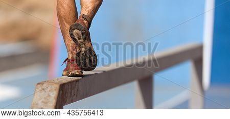 Mud Race Runners. Participant Walking On The Obstacle, Catches Balance
