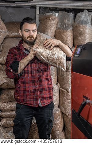 The Man Loads The Pellets In The Solid Fuel Boiler, Working With Biofuels, Economical Heating.