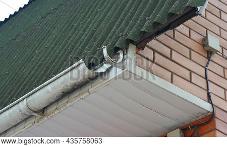 A Close-up Of A Roof With A Broken Roof Gutter And Soffit Open To Water Leaks.  A Damaged Rain Gutte
