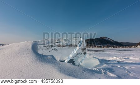 A Thick Transparent Ice Floe On A Frozen Lake. The Hummock Is Partially Covered With Snow. In The Di