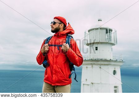 A Traveler On The Background Of A Lighthouse By The Sea. Portrait Of A Traveler In Red Clothes On Th
