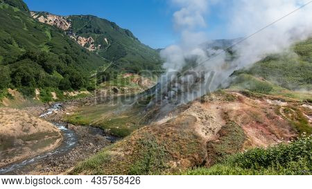 The River Flows Along A Rocky Bed In The Valley Of Geysers. Columns Of Steam From Hot Springs Rise A