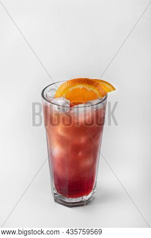 Beautiful Transparent Glass Of Summer Drink. Red And Yellow Lemonade With Ice And Orange Isolated On