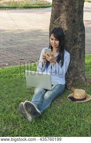 Asian Woman Sitting Green Garden Park Using Phone Listen Music From Smart Phone With Laptop Computer