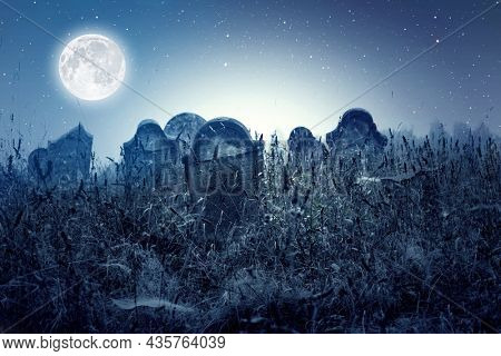 Tombstones in cemetery at night with full moon. Halloween concept.