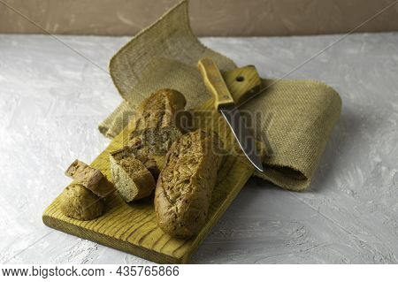 Two Fresh Rye Buns On A Cutting Wooden Board And A Piece Of Burlap One Of The Buns Is Cut There Is A
