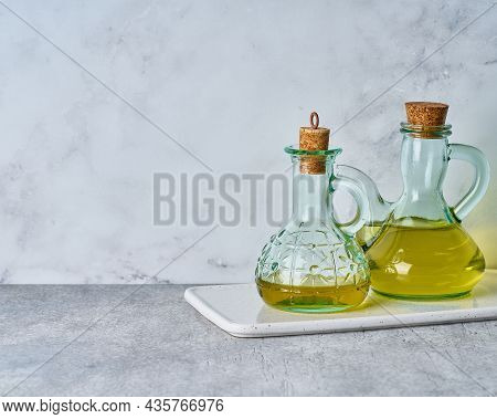 Set Of Extra-virgin Olive Oil Glass Bottles On White Texture Background. Golden Healthy Mediterranea