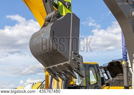 A Close-up Of A Lifted Excavator Bucket Against The Sky With Clouds. Construction Machinery At A Con