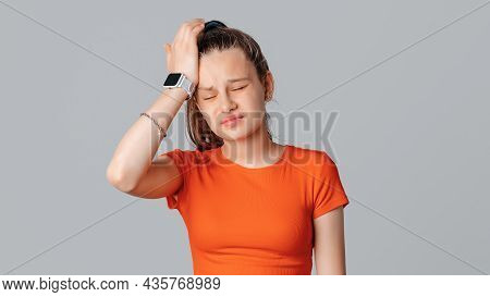 Portrait Of Pretty Girl And Dark Long Hair Wearing Orange T Shirt Having Tired Expression Holding He